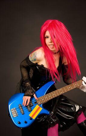 Girl showing tongue playing bass guitar photo