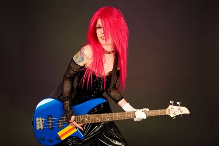 Attractive girl playing bass guitar isolated on black photo