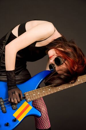 Crazy musician with bass guitar on black background  photo