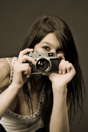 Young girl with retro camera, sepia old style  photo