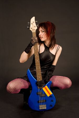 Attractive girl with bass guitar, studio shot photo