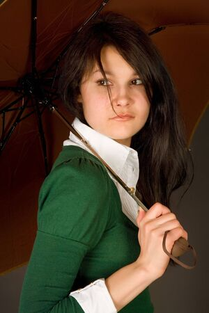 Serious looking girl in green sweater under umbrella photo