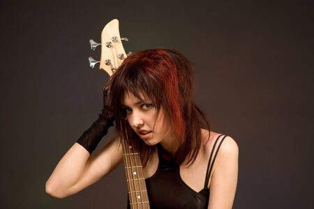 Sensual girl with bass guitar isolated in studio photo