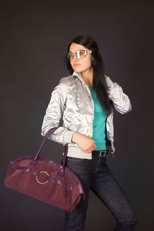 Fashion girl in designer glasses holding bag photo
