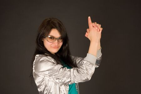 Smiling girl pointing her hands like a gun isolated on black background photo