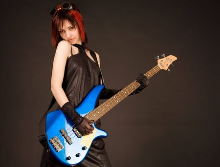 Rock girl in crazy outfit with bass guitar photo