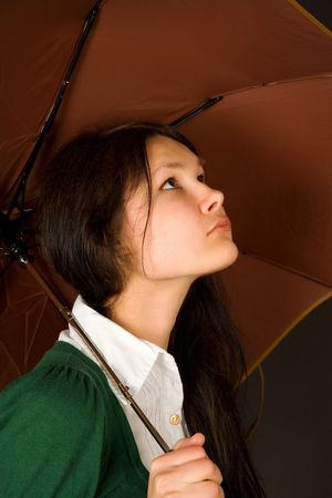 Serious looking girl under umbrella photo