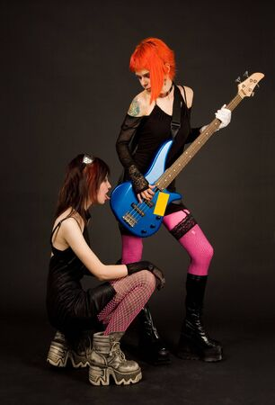 Two rock girls, one of them licking guitar, isolated on black background photo