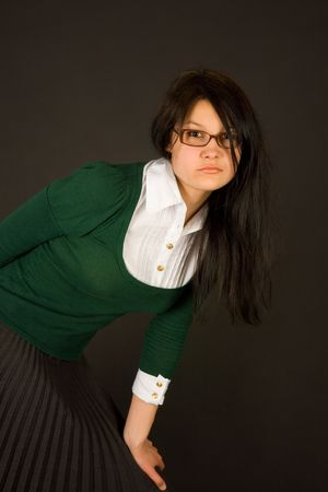 Serious looking girl dresses as teacher or businesswoman isolated on black photo