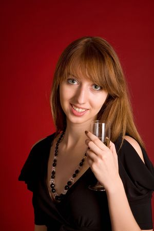 Sensual girl with champagne glass on dark red background  photo