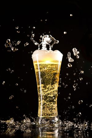 Beer glass with water splashes, isolated on black background