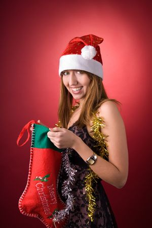Happy girl with Christmas stocking over red background photo