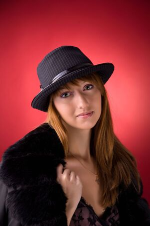 Romantic girl in stylish hat over red background photo