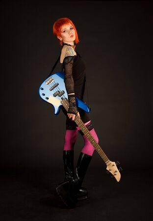 Rock girl with bass guitar, studio shot  photo