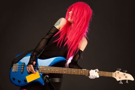 Smiling rock girl in crazy outfit with bass guitar  Stock Photo - 4794517