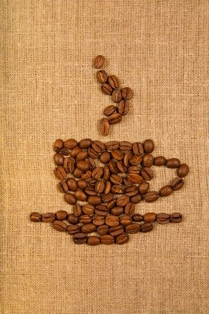 Coffee cup made of beans over light canvas background  photo