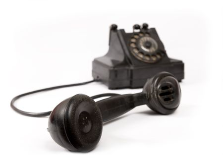 dialplate: Old black phone with scratches with receiver off the hook, selective focus