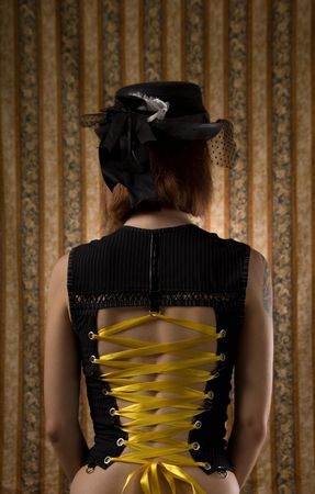 Girl in corset and vintage hat with veil, glamour wallpaper on background  photo