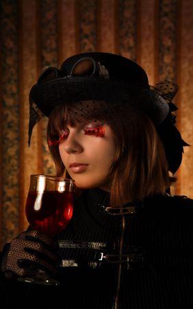 Fashionable girl with glass of wine and big false eyelashes  photo