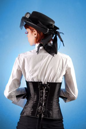 Rear view of beautiful girl in Victorian style clothes, studio shot over blue background