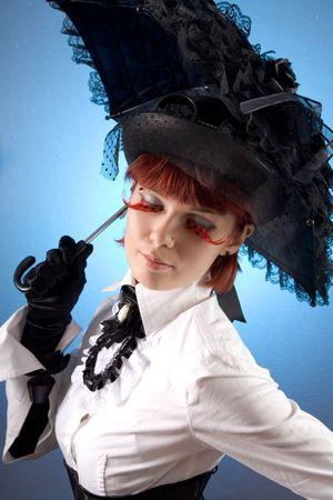 blusa: Hermosa chica en ropa de estilo victoriano con paraguas, foto de estudio sobre fondo azul