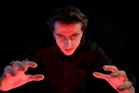 Scary vampire stretching his hands to catch a victim, isolated on black background Stock Photo - 5482005