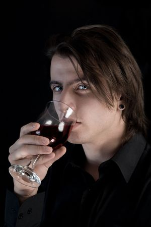 bloodsucker: Handsome pale vampire with blue eyes drinking wine or blood, Halloween theme