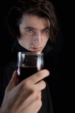 Handsome vampire with pale skin and blue eyes holding glass of wine or blood, Halloween theme