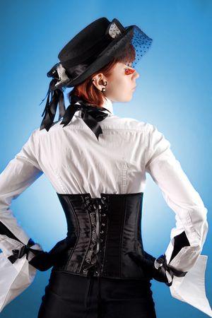 blusa: Vista trasera de la atractiva chica en ropa de estilo victoriano, foto de estudio sobre fondo azul Foto de archivo
