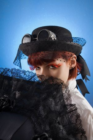 Attractive girl in Victorian style clothes with umbrella, studio shot over blue background  photo