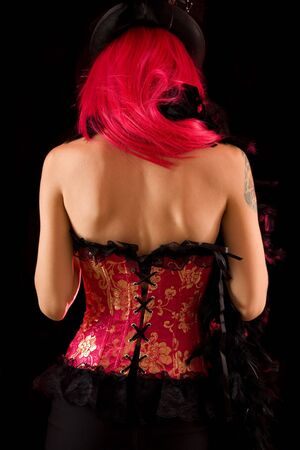 Rear view of cabaret girl in pink corset and hat, isolated on black background Stock Photo - 5613921