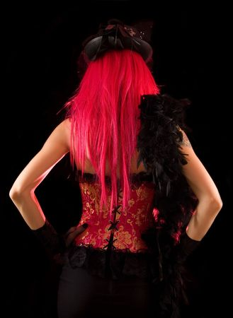 Rear view of cabaret girl in pink corset with feather boa, isolated on black background   photo