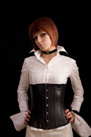 Attractive girl in white blouse and leather corset, isolated on black background  photo