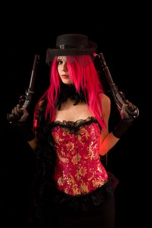Cabaret girl in pink corset with two guns, isolated on black background  photo