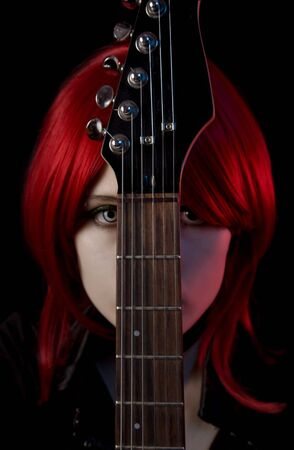 Portrait of gothic girl with guitar, selective focus on guitar, isolated on black background  photo