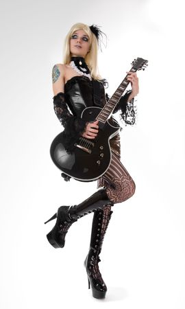 Sexy girl with guitar, focus on guitar and boots   photo