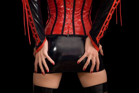 Close-up of girl in fetish miniskirt, isolated on black background