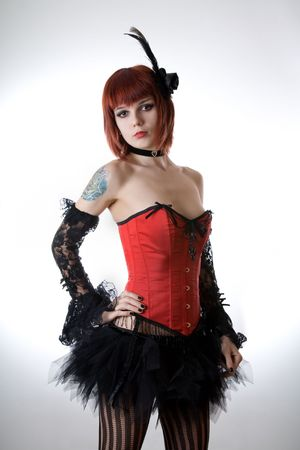 Cabaret girl in red corset, studio shot over light background  photo