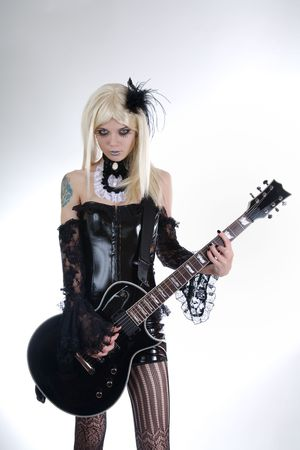 rock star: Alternative fashion girl playing guitar, studio shot over white background  Stock Photo