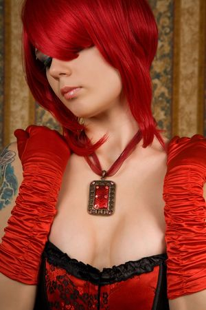 Attractive redhead woman in red corset, glamour background   photo