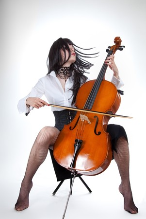 musician: Sensual girl playing cello and moving her hair, studio shot  Stock Photo