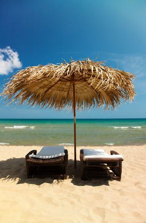 Two canvas chairs and umbrella on beautiful tropical beach  photo