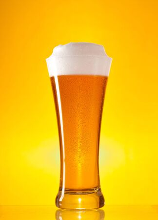 Full glass of beer with froth over yellow background Stock Photo - 7197792