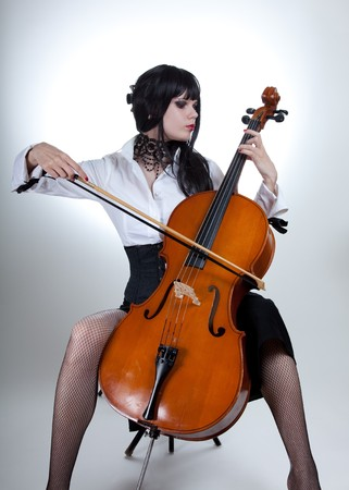 Romantic girl playing cello, studio shot over white background  photo