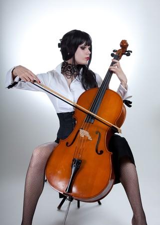 cellist: Romantic girl playing cello, studio shot over white background  Stock Photo