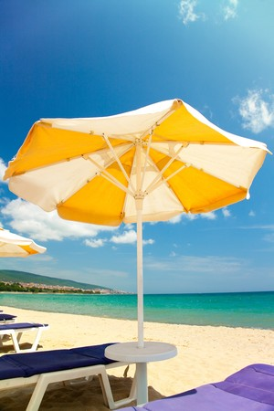 Bright umbrellas and chairs on beautiful tropical beach  photo