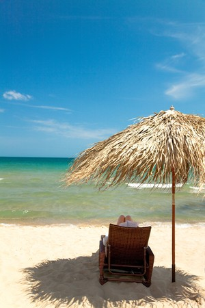 Unrecognizable person reading book in canvas chair on beautiful tropical beach  photo