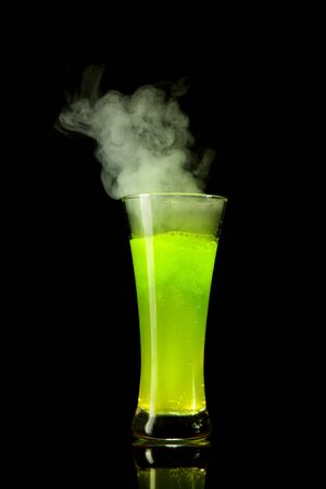 Boiling radioactive green alcohol with smoke, studio shot isolated on black background  Stock Photo - 7484942