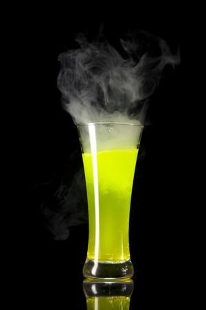 Yellow radioactive smoking alcohol, studio shot isolated on black background Stock Photo - 7484940
