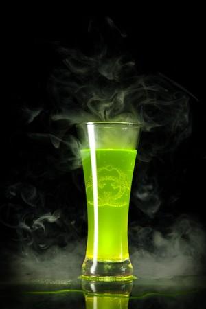 riesgo biologico: Alcohol radiactivo verde con el s�mbolo de riesgo biol�gico en su interior, aislado sobre fondo negro  Foto de archivo